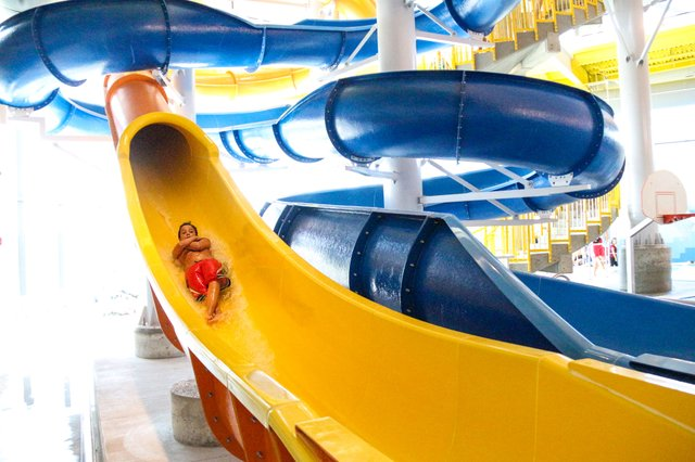 Lenexa Rec Center kid on indoor pool speed slide.JPG